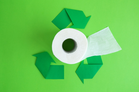 Flat lay of toilet paper with recycle symbol arrows on green background minimal creative ecology concept.