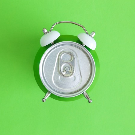 Flat lay of aluminum can in form of alarm clock on green background minimal creative concept.