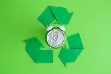 Flat lay of aluminum can in form of alarm clock and recycle symbol arrows minimal eco friendly creative concept.