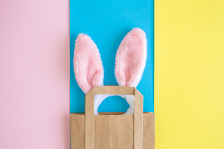 Flat lay composition of bunny ears out of shopping bag against colorful background minimal easter sale creative concept.