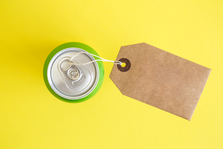 Flat lay of aluminum can with blank cardboard tag on yellow background minimal creative concept.