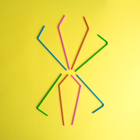 Flat lay of spider made of colorful drinking straws on yellow background minimal creative concept.