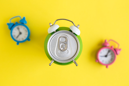 Flat lay of aluminum can in form of alarm clock and colorful alarm-clocks in the background on yellow minimal creative concept.