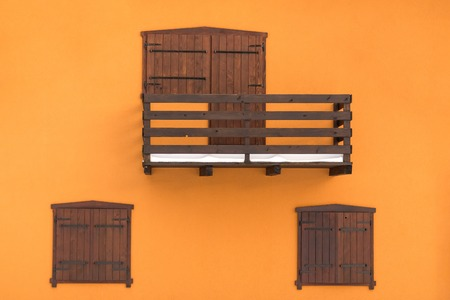 Wooden balcony with doors and windows on orange wall background minimal concept.