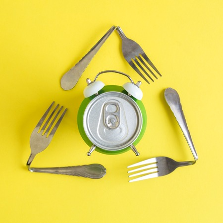 Flat lay of aluminum can in form of alarm clock and triangular eco recycle icon made of forks on yellow background minimal ecology creative concept.