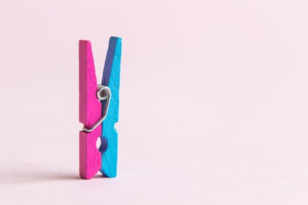 Close up of colorful clothespin against pastel pink background minimal creative concept. Space for copy.