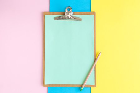 Flat lay of blank clipboard and pencil on colorful pastel background minimal creative concept.