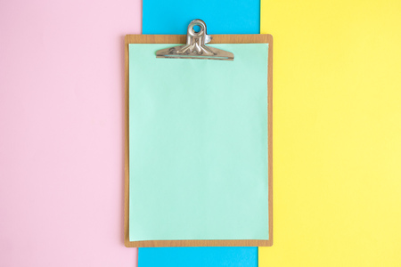 Flat lay of blank clipboard on colorful pastel background minimal creative concept.