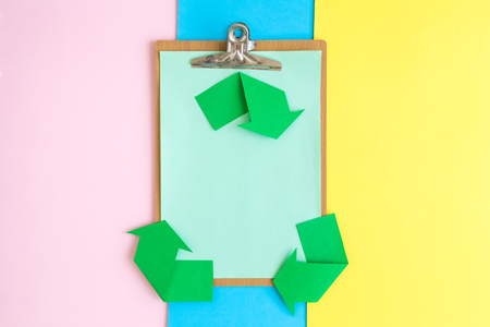 Flat lay of blank clipboard and recycle symbol made of paper on colorful background minimal creative ecology concept. Reklamní fotografie