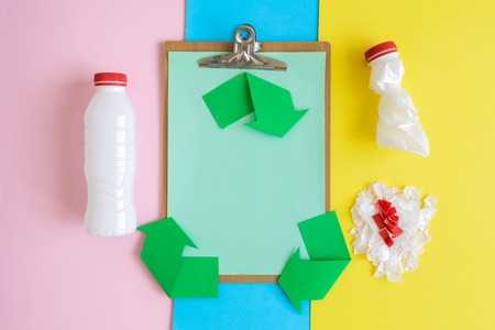 Flat lay of blank clipboard and recycle symbol made of paper with plastic bottles on colorful background minimal creative ecology concept.