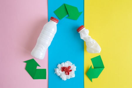 Recycle sign with plastic bottles isolated over pastel background minimal creative eco concept.