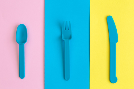 Plastic cutlery on multicolored background abstract. Reklamní fotografie