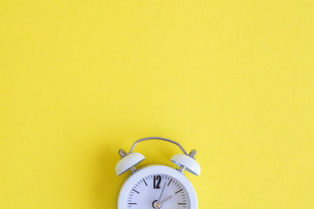 White clock on yellow background. Space for copy. Minimal concept. Reklamní fotografie
