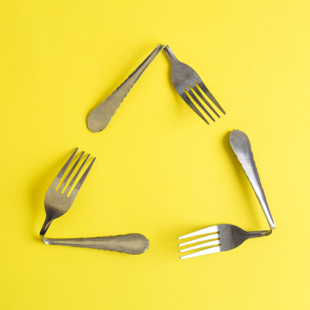 Triangular eco recycle icon made of forks on yellow background minimal ecology creative concept. Reklamní fotografie