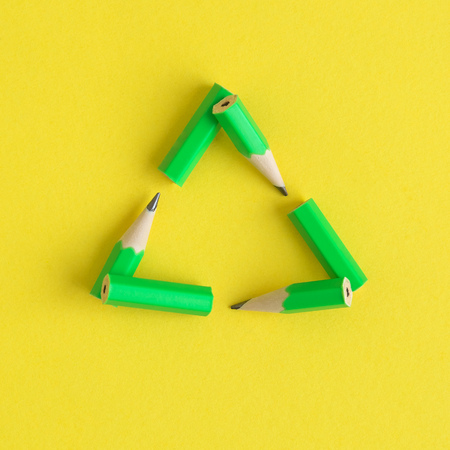 Flat lay of triangular eco recycle icon made of pencils on yellow background minimal creative eco concept. Reklamní fotografie