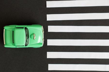 Flat lay of car toy on pedestrian crossing minimal creative concept.