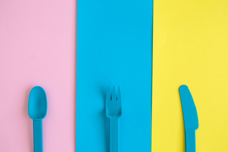 Flat lay of plastic spoon, fork and knife on colorful background minimal creative concept. Space for copy. Reklamní fotografie