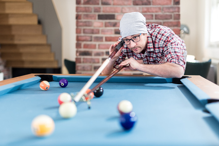 Portrait of handsome hipster guy aiming the white billiards pool snooker ball. Reklamní fotografie