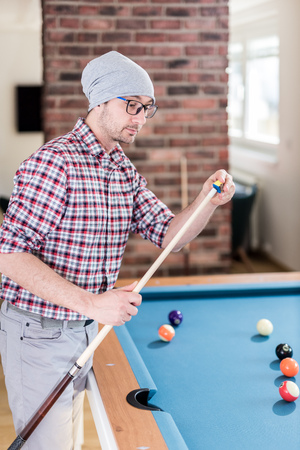 Hipster guy chalking the billiard cue at office chill room.