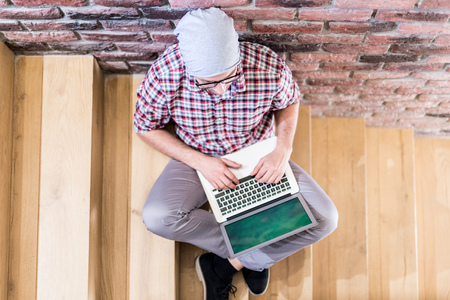 Top view of hipster working on laptop and sitting on stairs indoors.