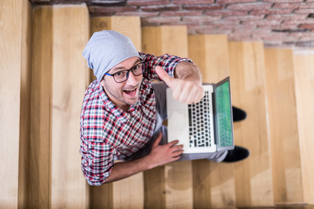Overhead view of modern hipster showing thumbs up while using laptop and sitting on stairs. Reklamní fotografie