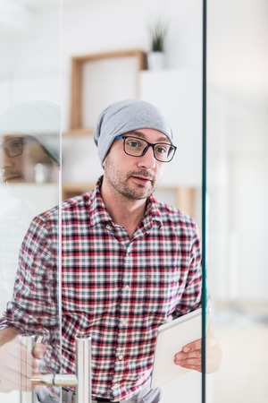 Portrait of fashionable architect or designer with tablet device opening glass office door.