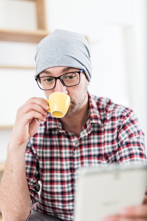 Close up portrait of urban fashionable man drinking coffee and using digital tablet device.