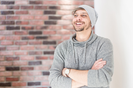 Young handsome smiling man with the beard in grey cap standing by the brick wall. Reklamní fotografie