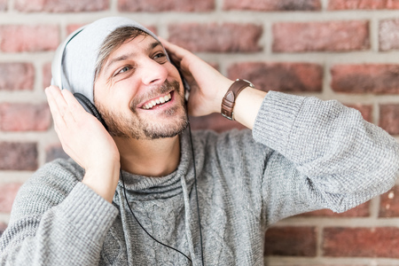 Fashionable hipster man in headphones and gray cap listening to music.