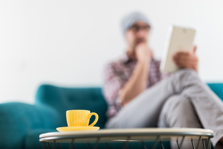 Close up of cup of coffee on table with modern man sitting on sofa and holding tablet in the background.