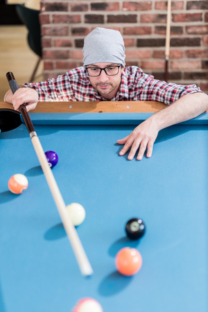 Hipster guy preparing for the next billiards shot.