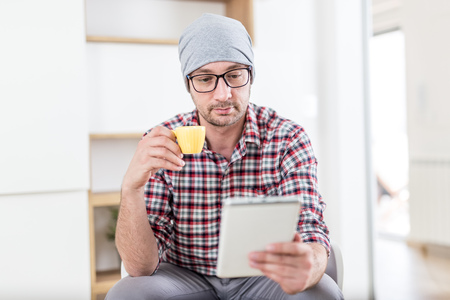Fashionable hipster businessman sitting at his office and holding cup of coffee and digital tablet.