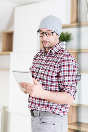 Portrait of young businessman holding digital tablet at modern office.