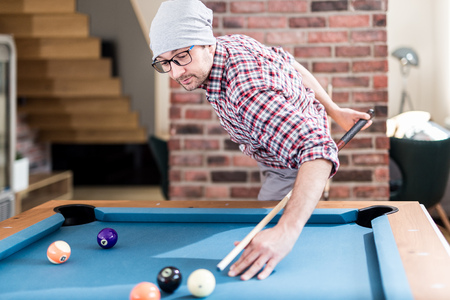 Fashionable hipster guy playing pool billiard game at the office chill room. Reklamní fotografie