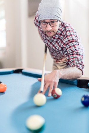 Portrait of hipster man playing billiards. Reklamní fotografie
