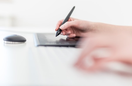 Close up side view of female holding digital pen and using graphic tablet at the desk.
