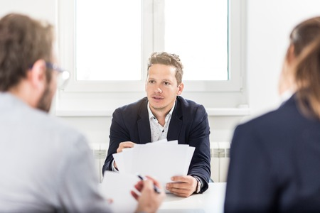 Portrait of young businessman discussing with his colleagues at the desk in meeting or conference room. Foto de archivo - 121692422
