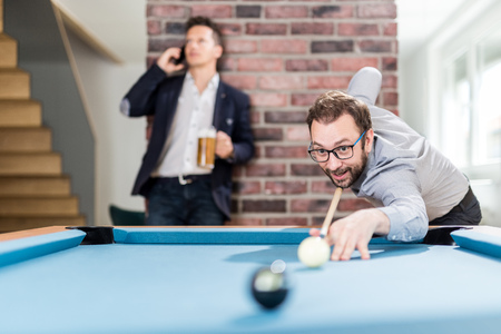 Business guys playing pool table billiard game in office chill room. Foto de archivo - 121692423