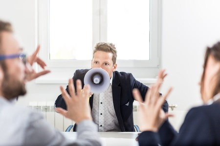 Businessman yelling at his colleagues by using megaphone on a meeting in the office. Foto de archivo - 121692425