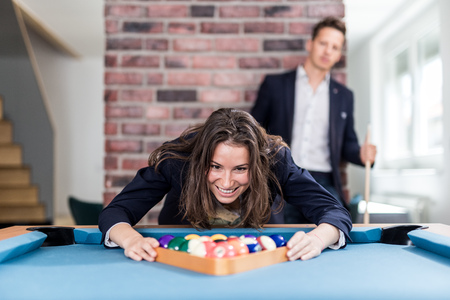 Portrait of young fashionable woman holding triangle wooden rack with pool balls on billiard table. Modern man in the background. Foto de archivo - 121692426