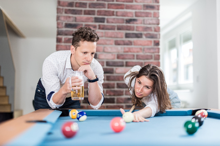 Couple playing snooker game and drinking beer. Foto de archivo - 122337558