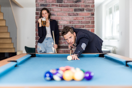 Beautiful fashionable couple playing pool table billiard game in office chill room. Foto de archivo - 122337561