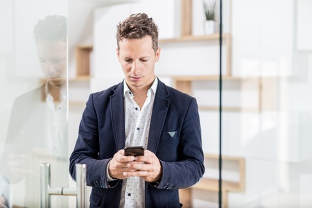 Fashionable business professional at office door using his mobile phone Foto de archivo - 122337563