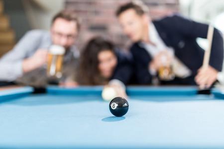 Cheerful billiard pool game winning team. Black ball in focus. Foto de archivo - 122337564