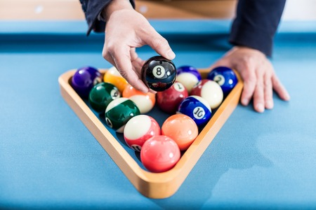Close up of man hand holding eight billiard ball above pool balls in wooden triangle on snooker table. Foto de archivo - 122337565