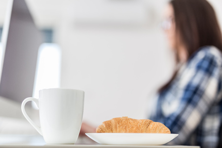 Cup of coffee and croissant on table and female worker in the background. Breakfast at office concept. Foto de archivo - 122337577