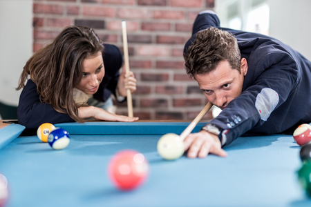 Young modern couple playing pool table billiard game. Foto de archivo - 122337578