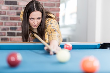 Portrait of young female playing billiards. Foto de archivo - 122337691