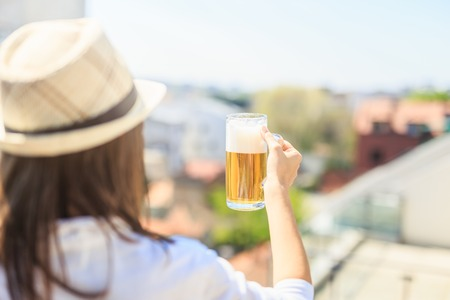 Rear view of hipster woman holding beer mug outdoors. Foto de archivo - 122337692