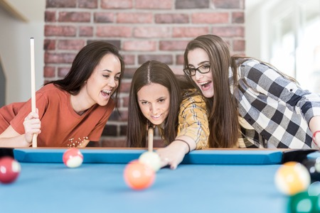 Cheerful female friends playing pool table billiard game at home. Foto de archivo - 122337693